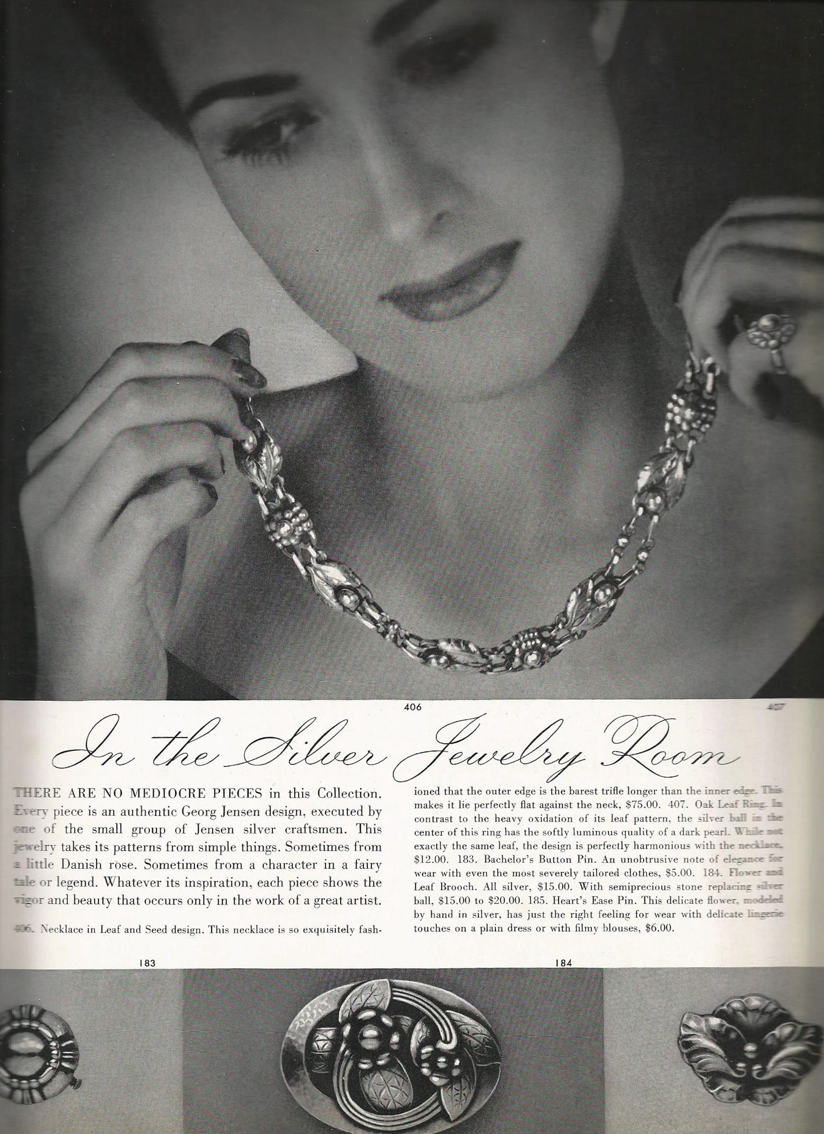 """Moving forward into the catalog, The next section of appeal is the jewelry section.    The text on the page is as follows:   """"In the Silver Jewelry Room  There are no mediocre piece in this Collection. Every piece is an authentic Georg Jensen design, executed by one of the small group of Jensen craftsmen. This jewelry takes its patterns from simple things. Sometimes from a little Danish rose. Sometimes from a character in a fairy tale or legend. Whatever its inspiration, each piece shows the vigor and beauty that occurs only in the work of a great artist.  406. Necklace in Leaf and Seed design. This necklace is so exquisitely fashioned that the outer edge is the barest trifle longer than the inner edge. This makes it lie perfectly flat against the neck, $75.00. 407. Oak Leaf Ring. In contrast to the heavy oxidation of its leaf pattern, the silver ball in the center of this ring has the softly luminous quality of a dark pearl. While not exactly the same leaf, the design is perfectly harmonious with the necklace, $12.00. 183. Bachelor's Button Pin. An unobtrusive note of elegance for wear with even the most severely tailored clothes, $5.00. 184. Flower and Leaf Brooch. All silver, $15.00. With semiprecious stone replacing silver ball, $!5.00 to $20.00. 185. Heart's Ease Pin. This delicate flower, modeled by hand in silver, has just the right feeling for wear with the delicate lingerie touches on a plain dress or with flimy blouses, $6.00."""""""