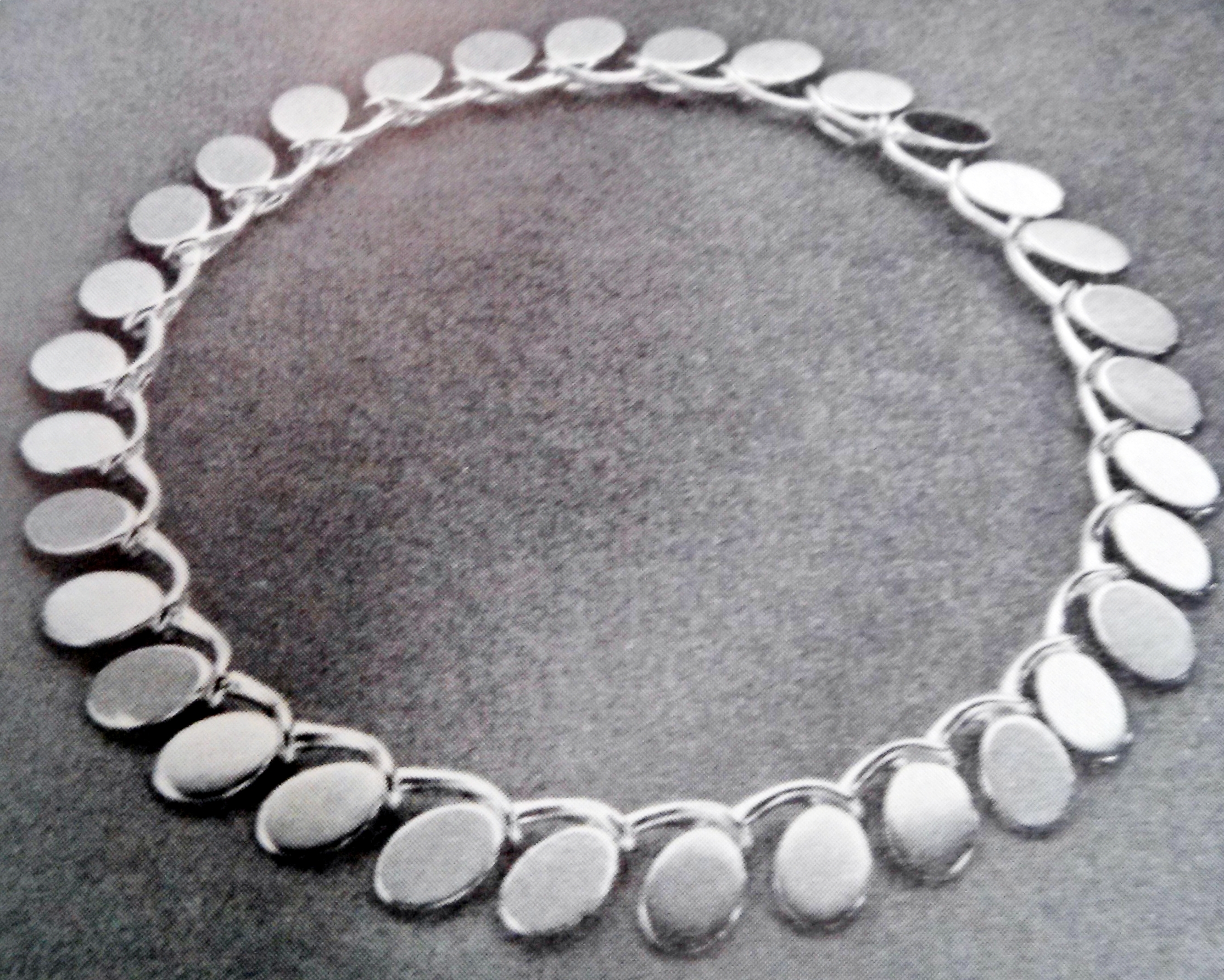 """""""The necklace shown in silver from Bent Gabrielsen was designed in 1957 for the Hans Hansen Silversmithy in Koldinghus. The necklace uses a clear yellow enamelling on the front, with black enamel on the clasp. Each link is identical to the next, and grasp each other like holding hands in a long chain. The piece represents a clearly thought out plan using an organic shapes to create interlocking grommets and insert as part of the links, separating it from your average chain jewelry."""" - Translated from the text accompanying the photo."""