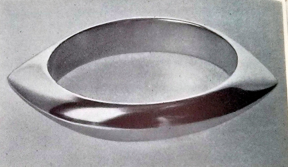 A gold bracelet designed by Nanna and Jorgen Ditzel and executed by Axel Jensen in 1956 for Georg Jensen. The bangle itself is almost symbolic of jewelry of its time. Its simple design made it incredibly versatile and able to pair with a variety of different women's wear. The hollowed shape and clean surface suggests an incredible strength and modernity in the design, yet also hearkens back to more primitive jewelry designs.