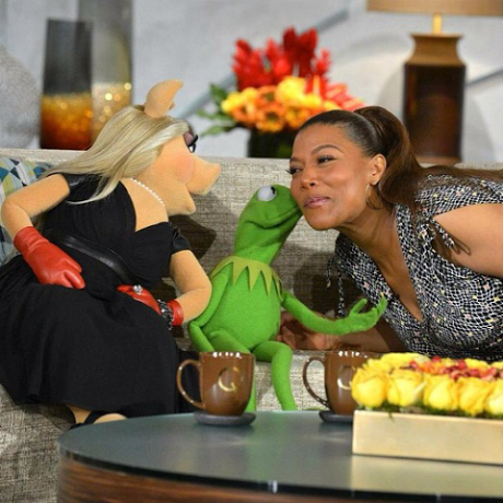 Kermit the Frog kissing Queen Latifah with Miss Piggy on the left