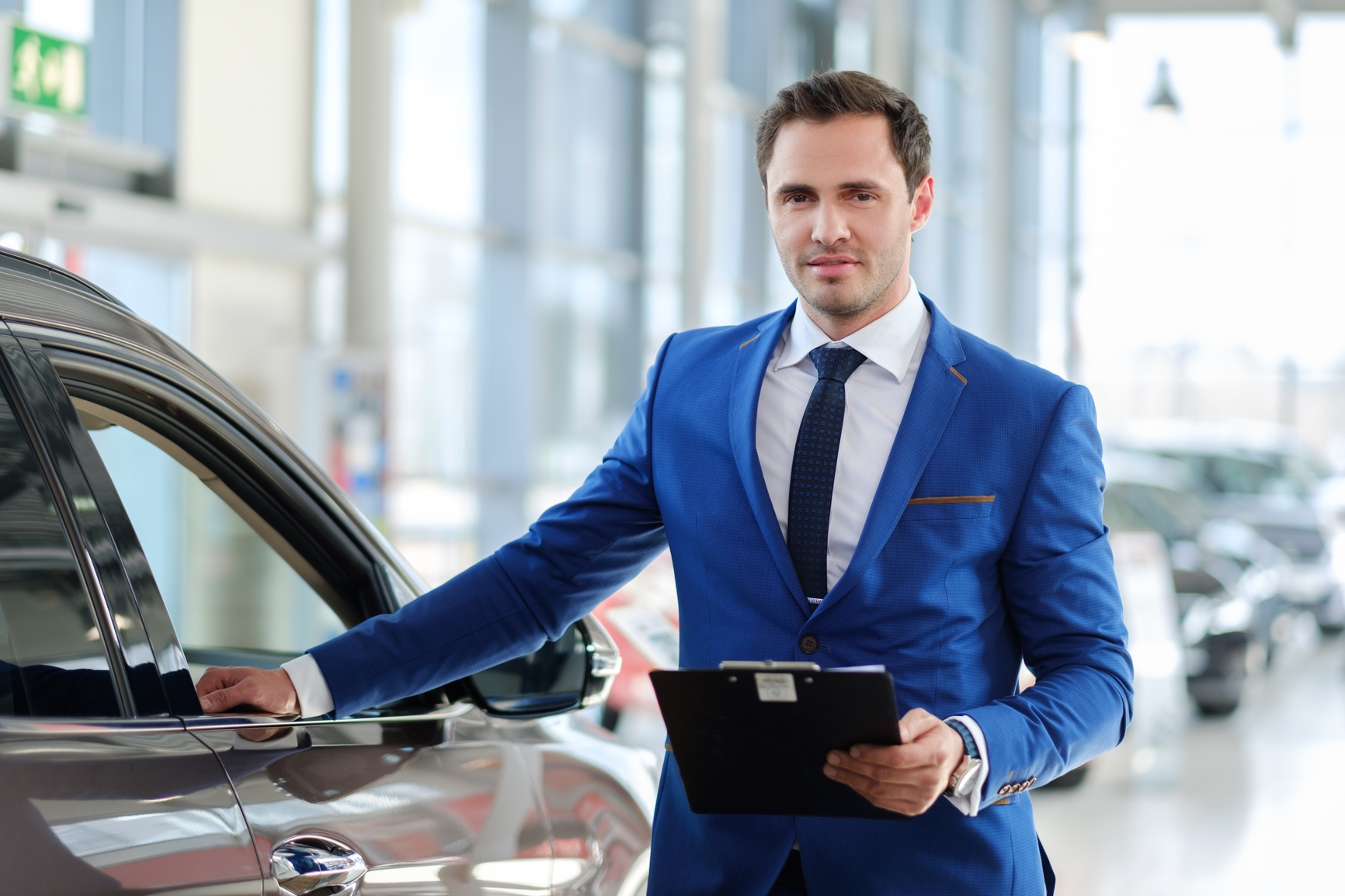 photodune-15689236-confident-young-car-dealer-standing-in-showroom-m (1).jpg