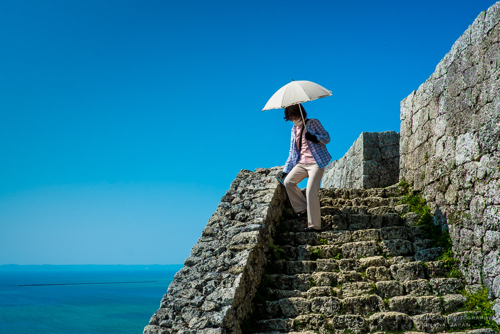 An Okinawan women holding an umbrella to shield herself from the sunlight descends the steep stairs of Katsuren Castle ruins. Okinawa, Japan