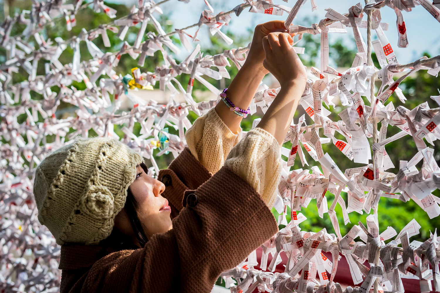 A woman ties her Omikuji onto a line at a shrine in Okinawa, Japan. Omikuji are traditional Fortune-telling papers purchased at shrines in Japan during Hatsumode (A person's first shrine visit of the year).
