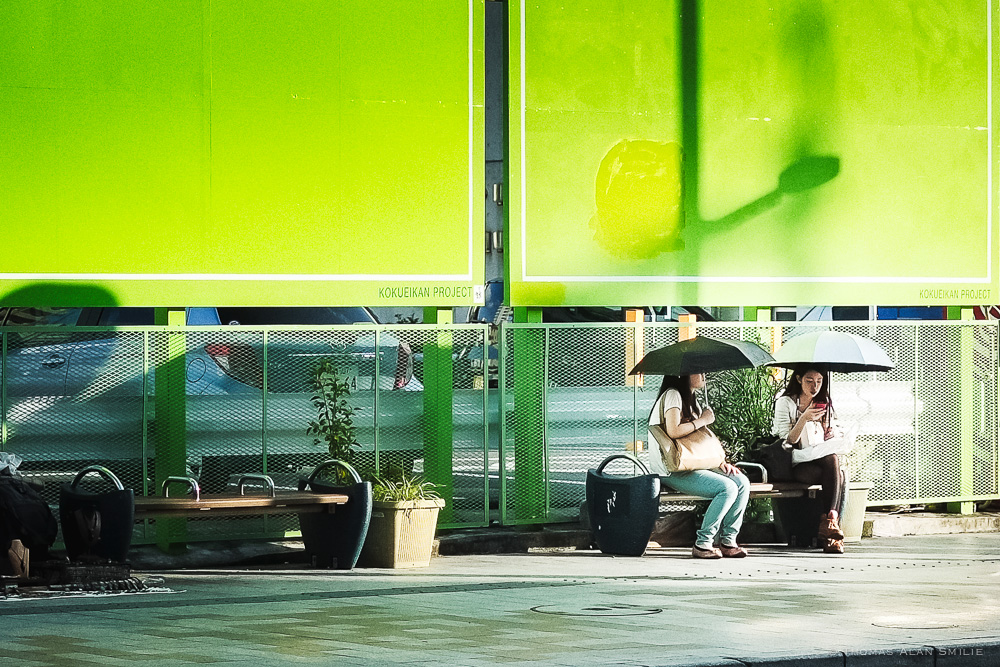 Two women use their umbrellas to shield themselves from the sun while waiting for the bus on Kokusai Street in Naha. Fuji X-Pro1, 35mm f/1.4