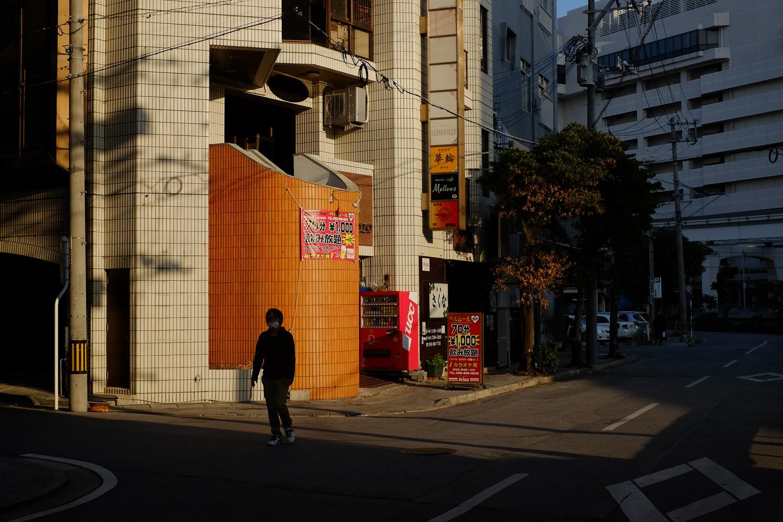 A man walking in Naha, Okinawa, Japan. Fuji x100s w/ TCLx100 Teleconverter at ISO 400, f5.6, 1/1500 sec.