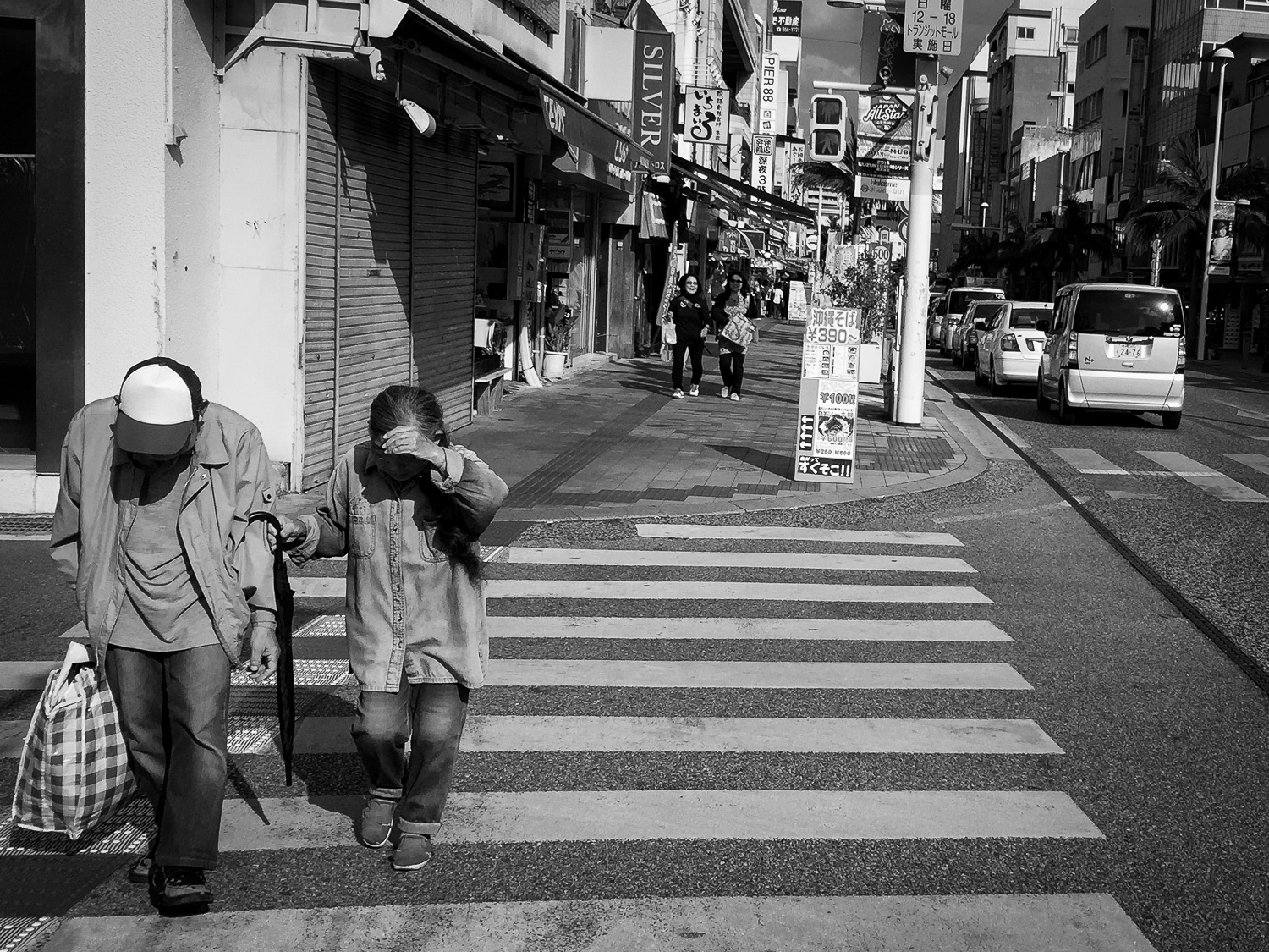 An elderly couple crossing the street in Naha, Okinawa, Japan. Apple iPhone 6 Plus at ISO 32, f2.2, 1/4000 sec. Converted to black and white in Lightroom Mobile.