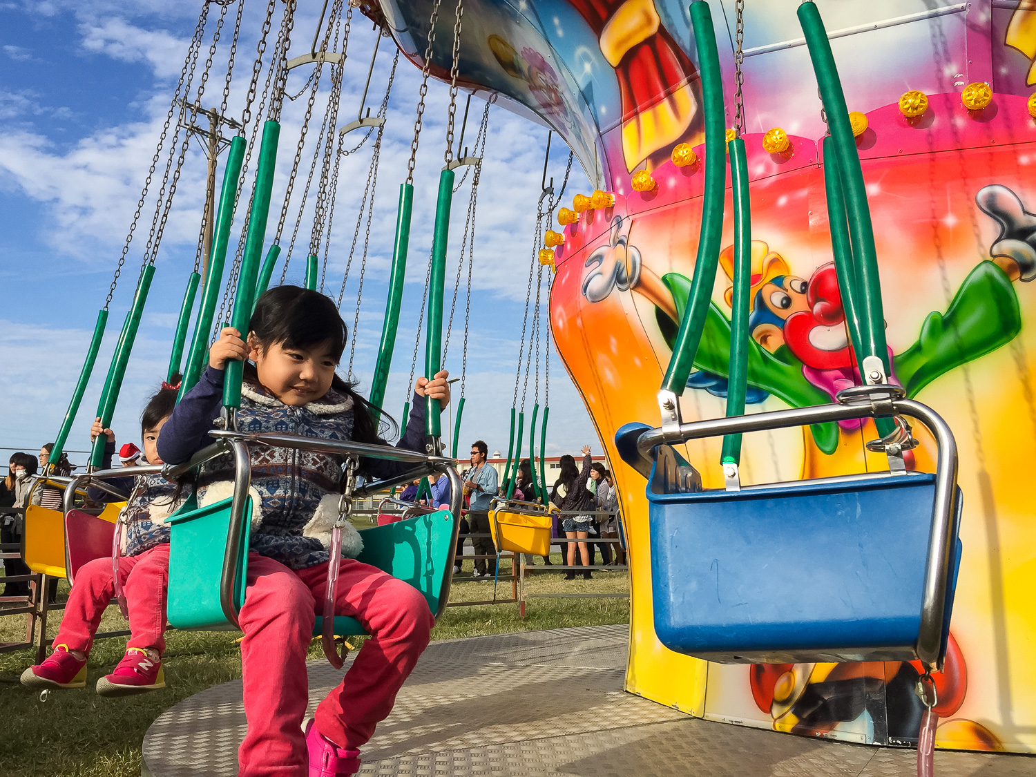 A little girl on a ride at a festival in Okinawa, Japan. Apple iPhone 6 Plus, ISO 32, f2.2, 1/1700 sec.