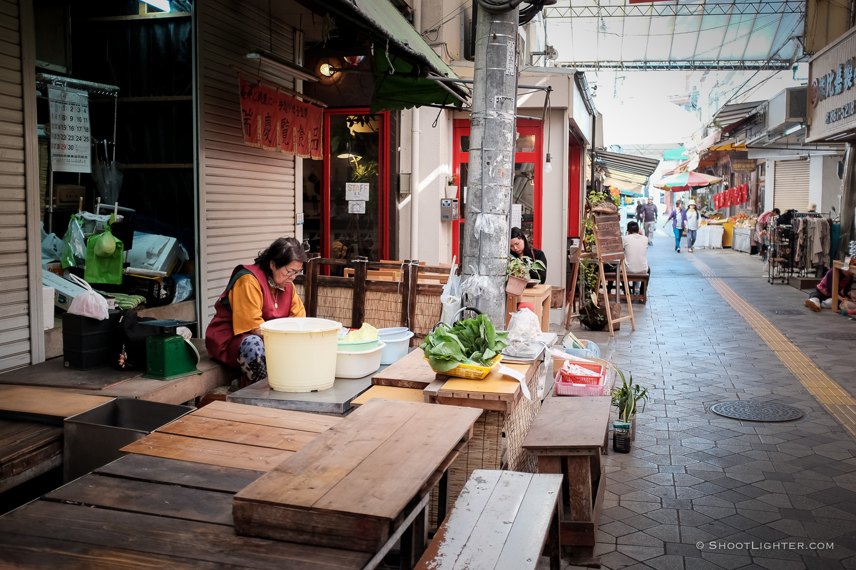 An elderly lady sells vegetables in Naha, Okinawa Japan. Fujfilm x100T, ISO 320, f/2.0, 1/60 sec, Fujifilm chrome film emulation, edited in Adobe Lightroom 6.