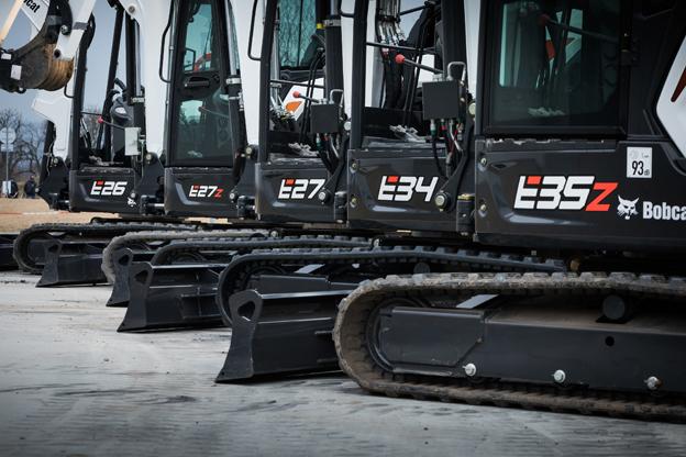 Ces 5 nouveaux modèles Série R  -     E26, E27z, E27, E34     et     E35z-    offrent une combinaison idéale de forces d'arrachement élevées, de stabilité exceptionnelle et de précision de commande tout en gardant des poids opérationnels réduits qui facilitent le transport. Ces mini pelles bénéficient de nombreuses fonctionnalités à la pointe de la technologie et offrent un niveau exceptionnel de qualité et de robustesse. Elles sont basées sur de nouvelles plateformes adaptables qui permettent différentes configurations et spécifications que le client peut combiner à sa guise de sorte à obtenir la machine qui répond idéalement à ses besoins. Ces machines sont taillées sur mesure pour des utilisateurs spécifiques. Ainsi la  E26  est particulièrement destinée à la location. Son poids de transport a été réduit de 100kg mais sa capacité de levage sur le côté a augmenté. En plus, elle bénéficie du vérin de flèche monté à l'intérieur de la flèche (C.I.B) une exclusivité Bobcat. Autre modèle la  E27z  une véritable pelle à  orientation sans déport  (ZHS), même avec le contrepoids lourd en option. Elle bénéficie des performances de fouille et un confort de l'opérateur typiques de pelles de bien plus grande taille. Quant à la  E34 , de 3,4 tonnes à déport conventionnel elle présente une stabilité accrue, des performances impressionnantes et des commandes encore plus précises. Avec sa nouvelle cabine grand confort et la puissante climatisation en option, l'opérateur bénéficiera de conditions de travail idéales par tous les temps. Avec la  E35z , une pelle compacte dans la catégorie très demandée des 3,5 tonnes, Bobcat offre l'avantage supplémentaire de l'orientation sans déport (ZHS.) C'est la plus grande des pelles de la gamme Série R. Les  E34  et  E35z  sont également les seules machines de leur catégorie à disposer de l'option de tension hydraulique automatique des chenilles, une fonctionnalité qui simplifie encore davantage leur entretien et minimise les risques de déche