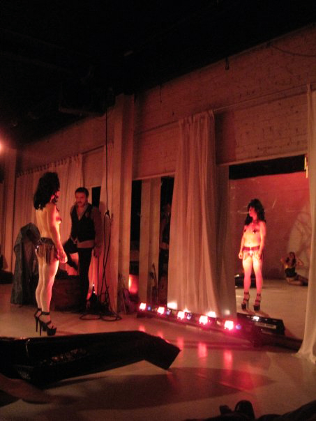 Trixxie Carr (Tiny Dionysus), Stanley Frank (Chorus).    Scenic Design by Maya Linke and Ben Randle, Lighting Design by Anthony Powers.