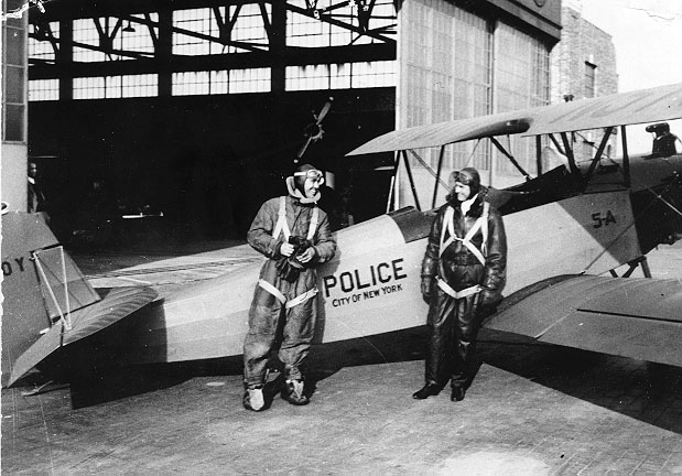 Two NYPD Officers pose with their open cockpit Bi-Plane at Floyd Bennett Field in the early days of police aviation. Brooklyn NY