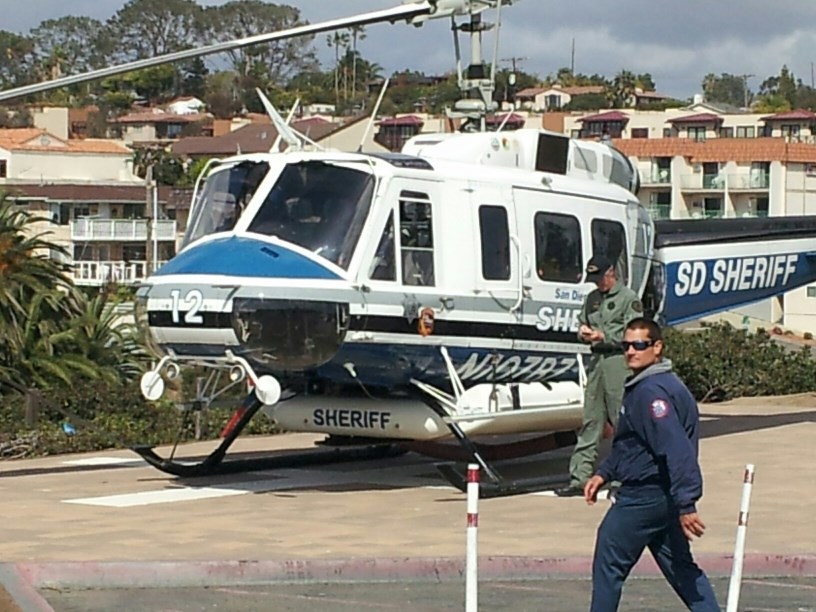 Copter 12 on the Landing Pad at Moonlight State Beach, Encinitas Ca., Instructor Pilot T. Webber standing next to the Helicopter; 2014.
