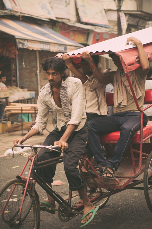 Men transporting a sheet of corrugated iron on a rickshaw