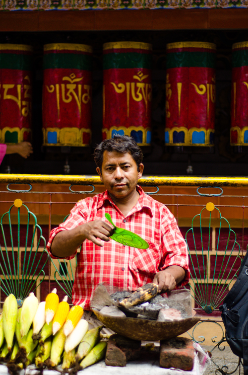 Man selling chargrilled corn in front of prayer wheels