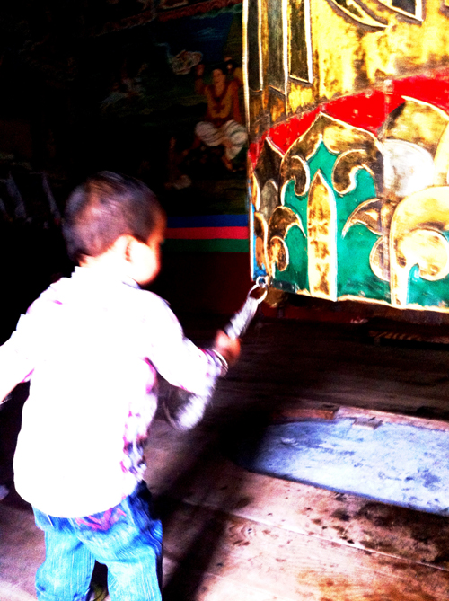 A young, and beautiful, boy spinning a large prayer wheel inside a temple