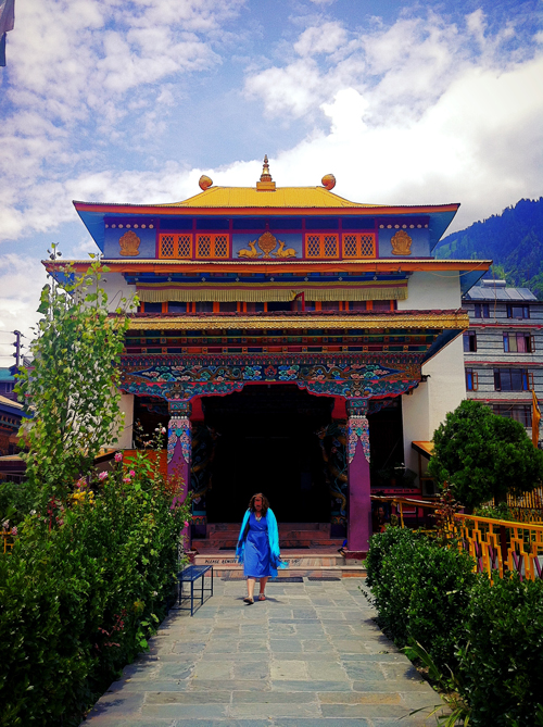 Mikayla walking in front of the Nyinmapa temple - inside is a two story golden statue of Buddha