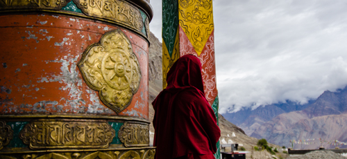 Monk by the prayer wheel outside the quiet gompa at Hunder