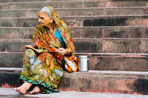 A woman with her prayer book on the ghats