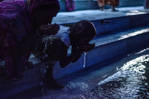 Mother and daughter drinking the purifying waters of the Ganga