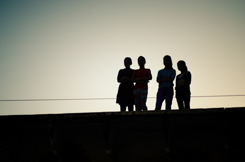 Girls watch from a rooftop