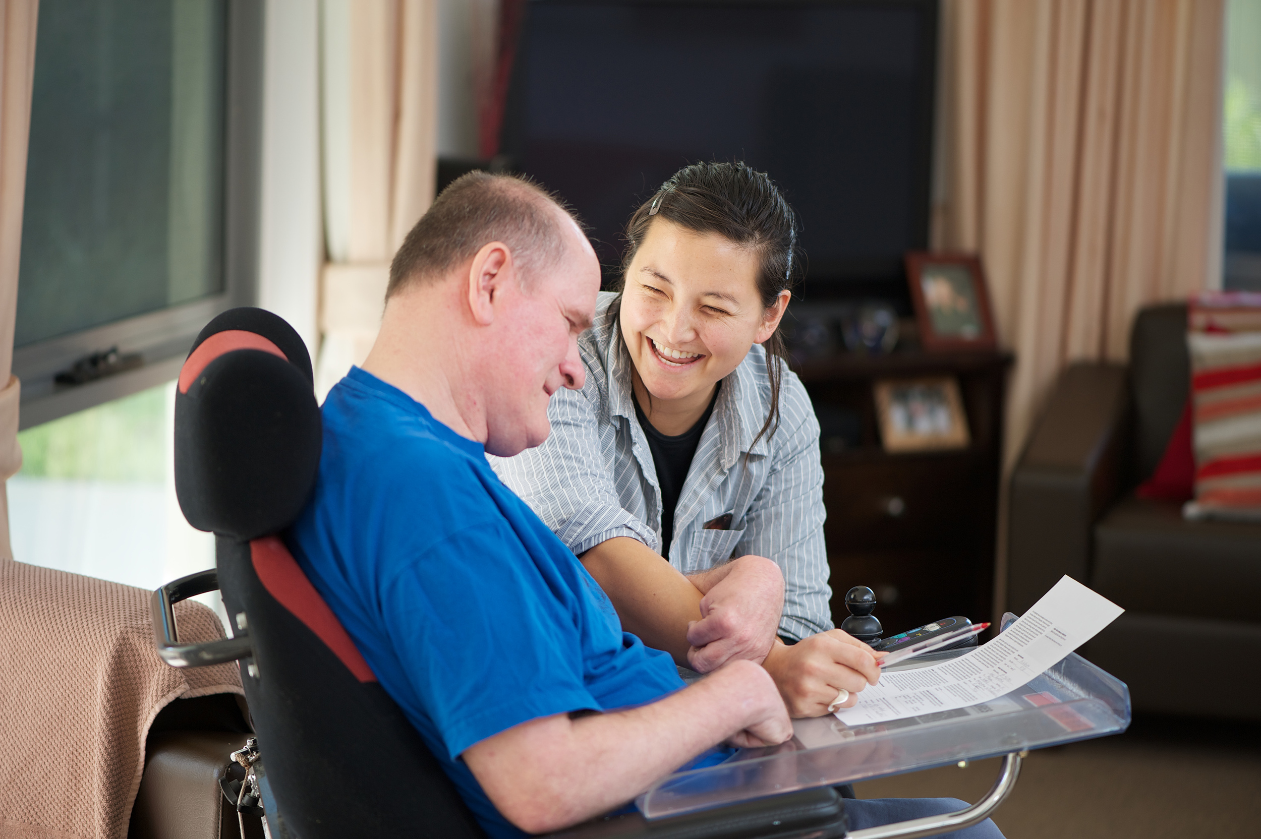 staff member smiling with a man in an electic wheelchair.jpg