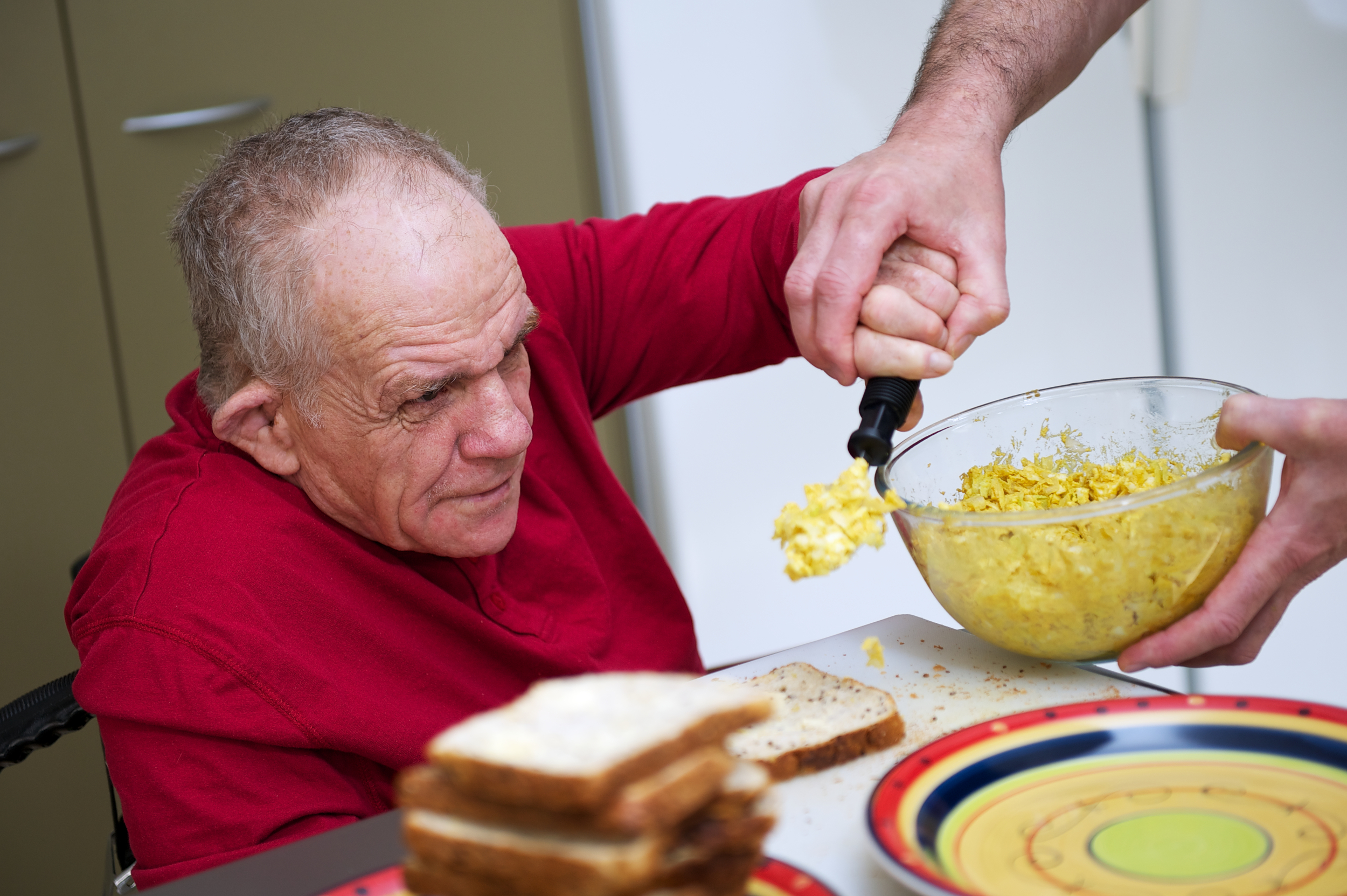 senior man with a disability being helped in kitchen.jpg