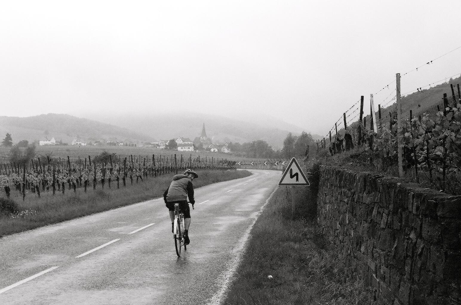 Seth riding his handbuilt randonneur bicycle in Alsace, France.