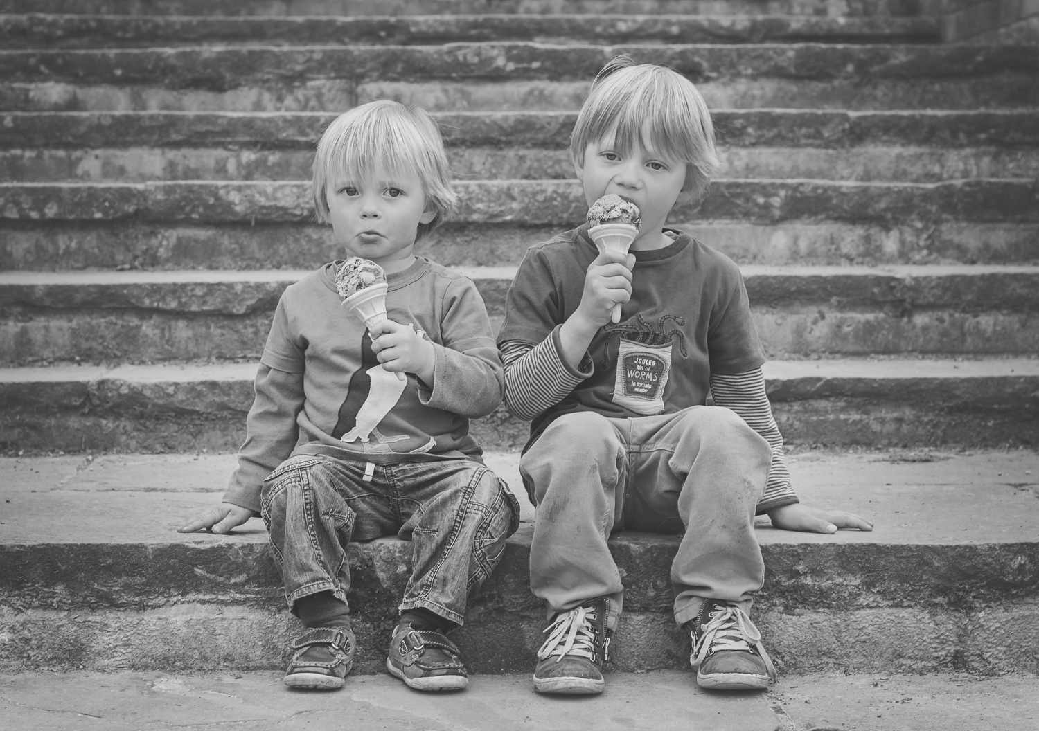 Two brothers sit on the steps messily eating ice cream at Dunorlan Park in Tunbridge Wells