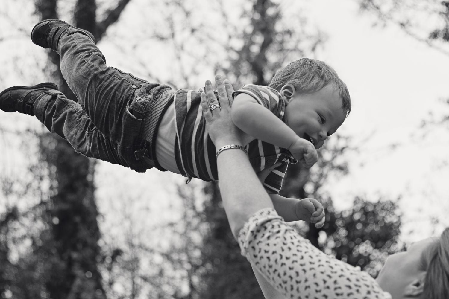 Black and white image of a mum swinging her 2 year old in the air by Chalybeate Spring in Tunbridge Wells