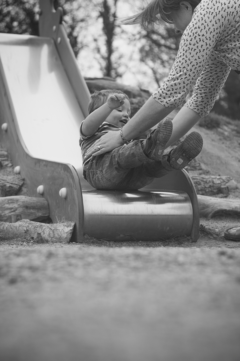 Fun family photoshoot showing a little boy playing on the slide in the park in Dunorlan