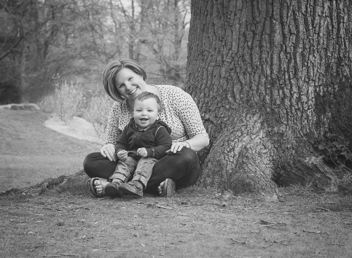 Fine art black and white portrait of a mother and son sitting on a grassy slope at Dunorlan Park