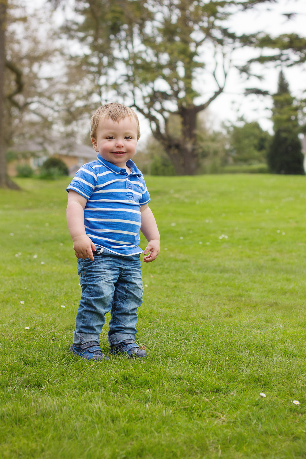 Little boy in jeans and a blue striped top having fun at an on-location photoshoot at the park