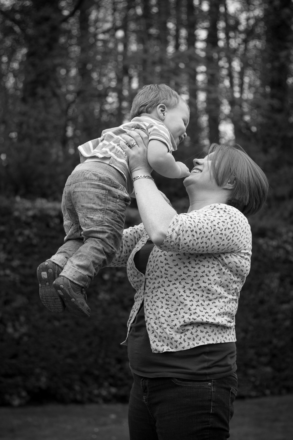 Mum lifting up her toddler into the air and smiling