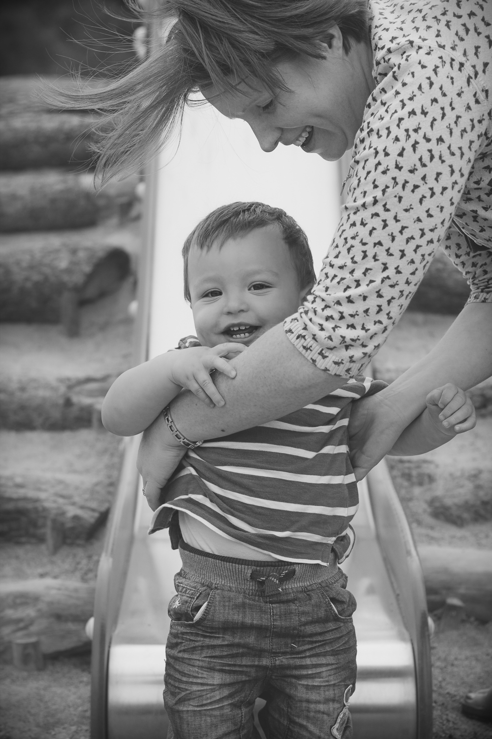Mum and 2 year old boy on a family photo session at the park - the boy has just jumped off the slide and has been caught in the arms of his mama