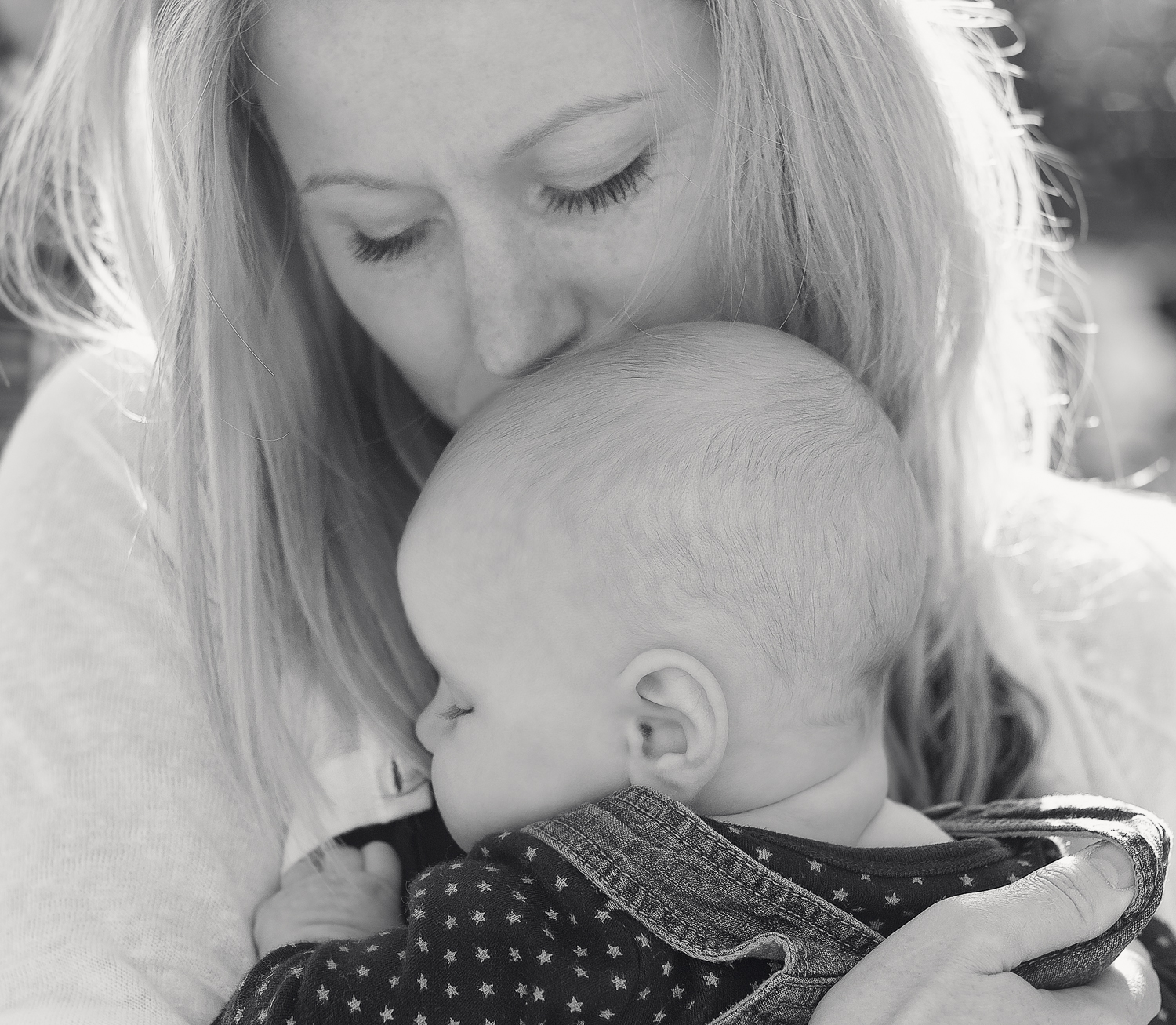 Close-up matte black and white image of a Mother and baby boy cuddling