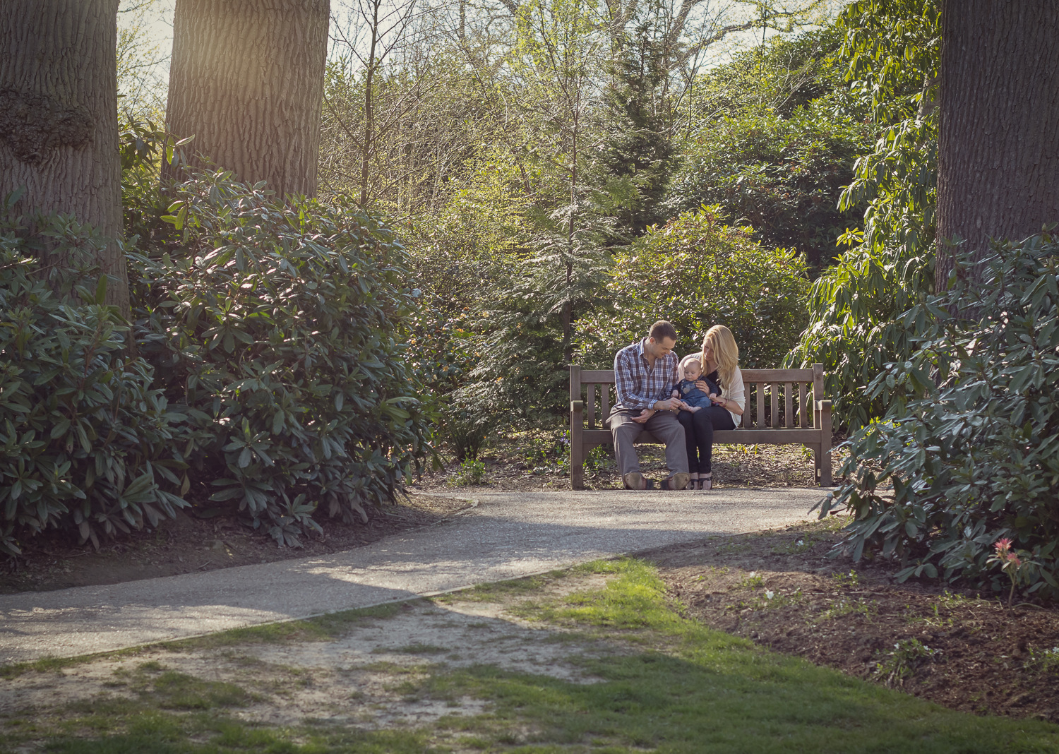 Landscape photograph at the beautiful Dunorlan Park in Tunbridge Wells, displaying a Mum, Dad and their little boy resting on a bench