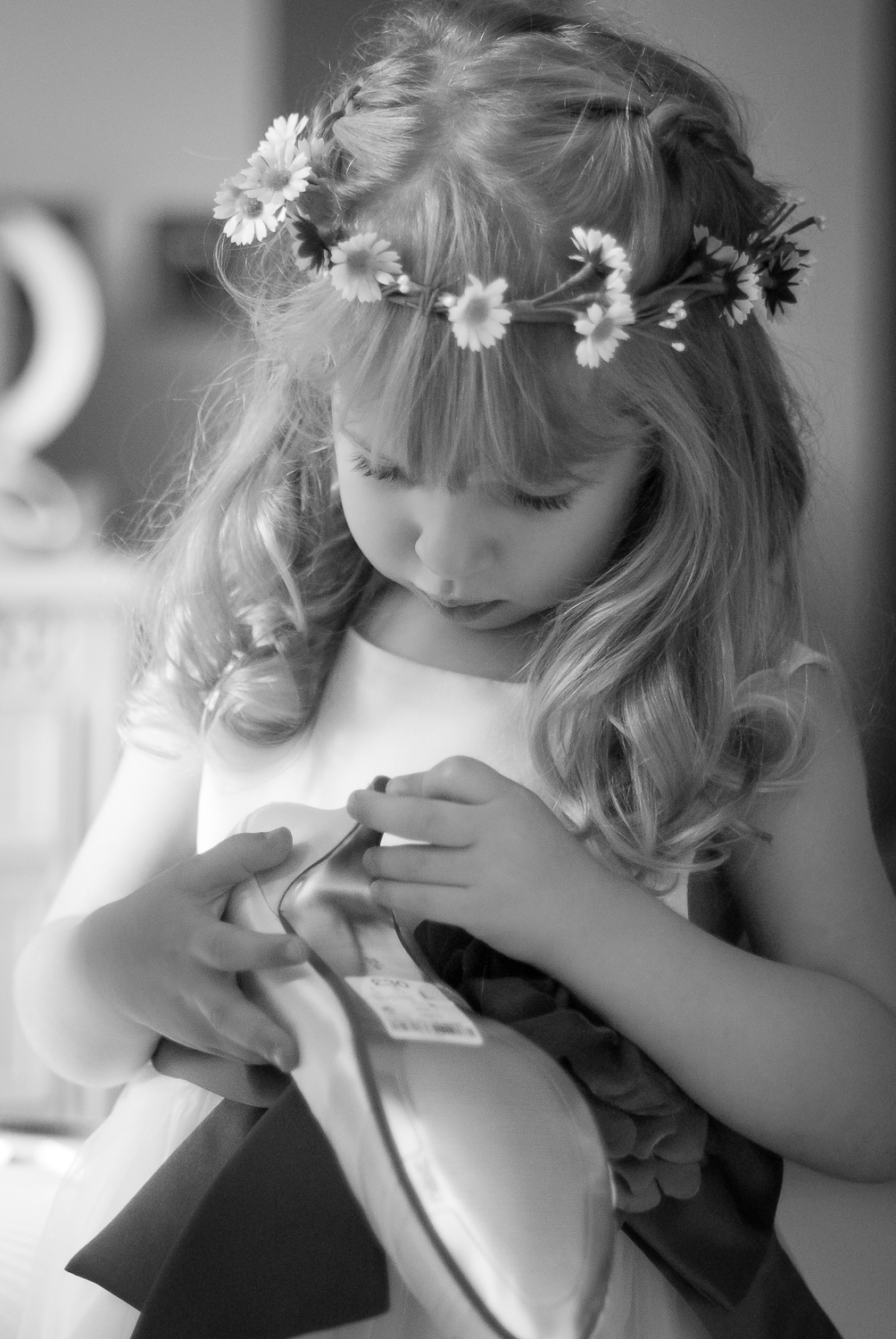 Photograph of a child bridesmaid examining her Mum's wedding shoe