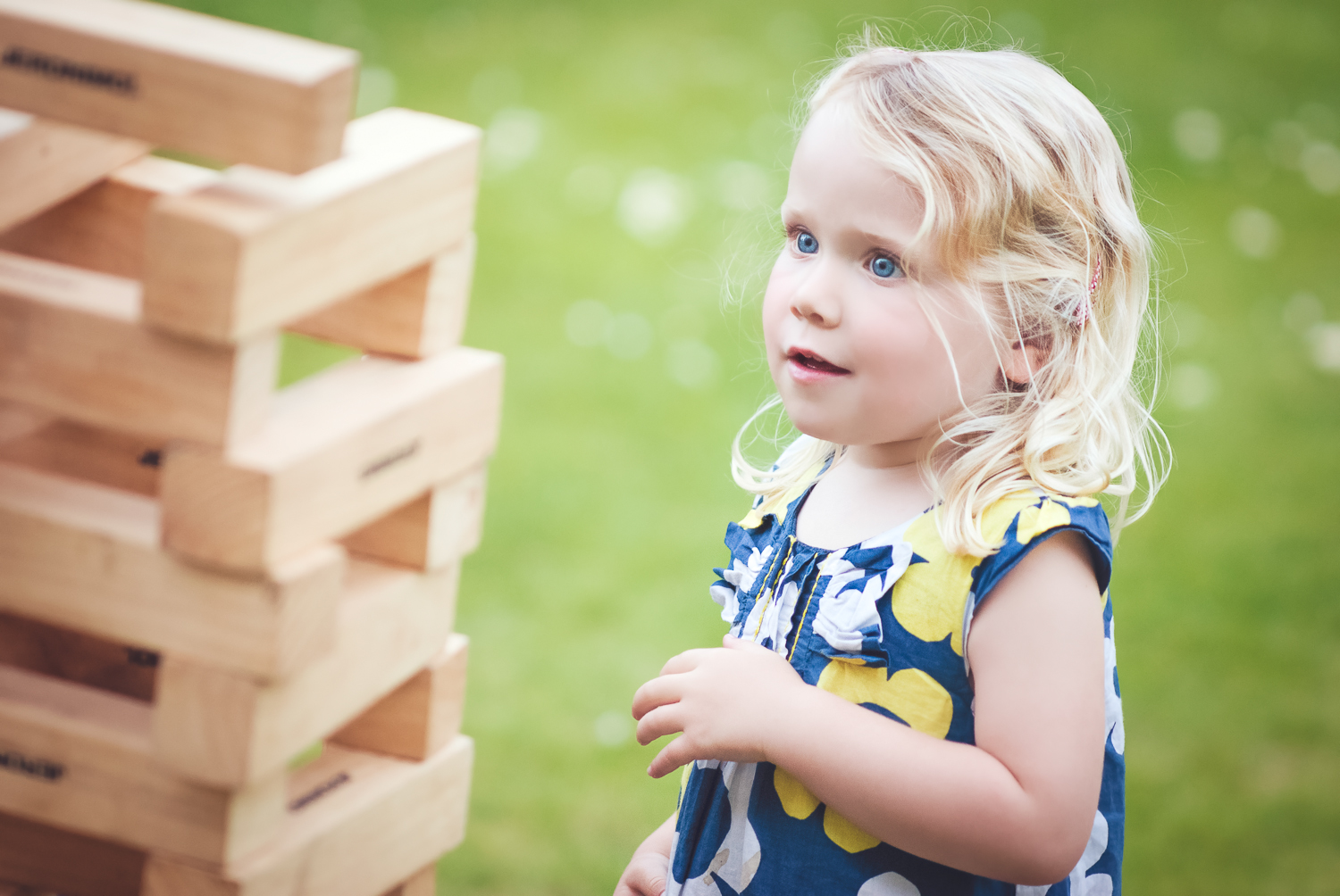 A little girl playing outdoor giant jenga at a wedding party