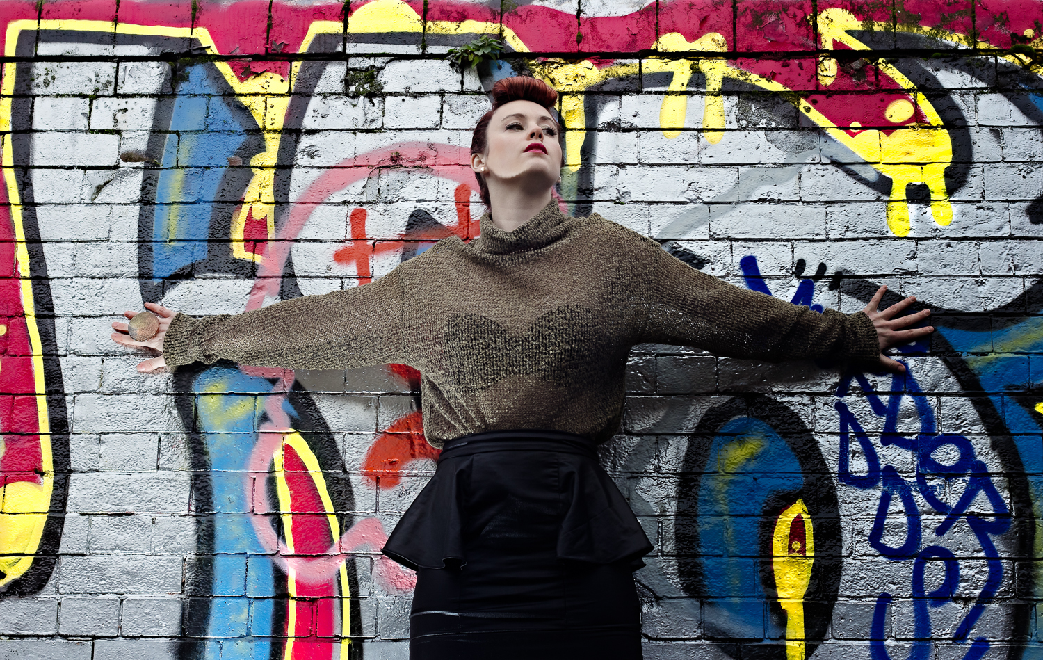 An up and coming Australian pop singer poses at the Banksy tunnel in London, with her eye catching red hair contrasting with the yello graffitied wall