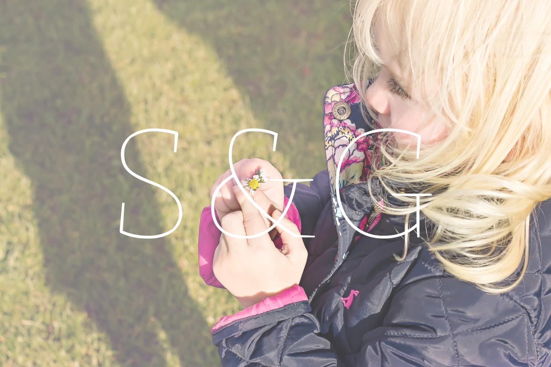 Photograph of a little girl holding a daisy