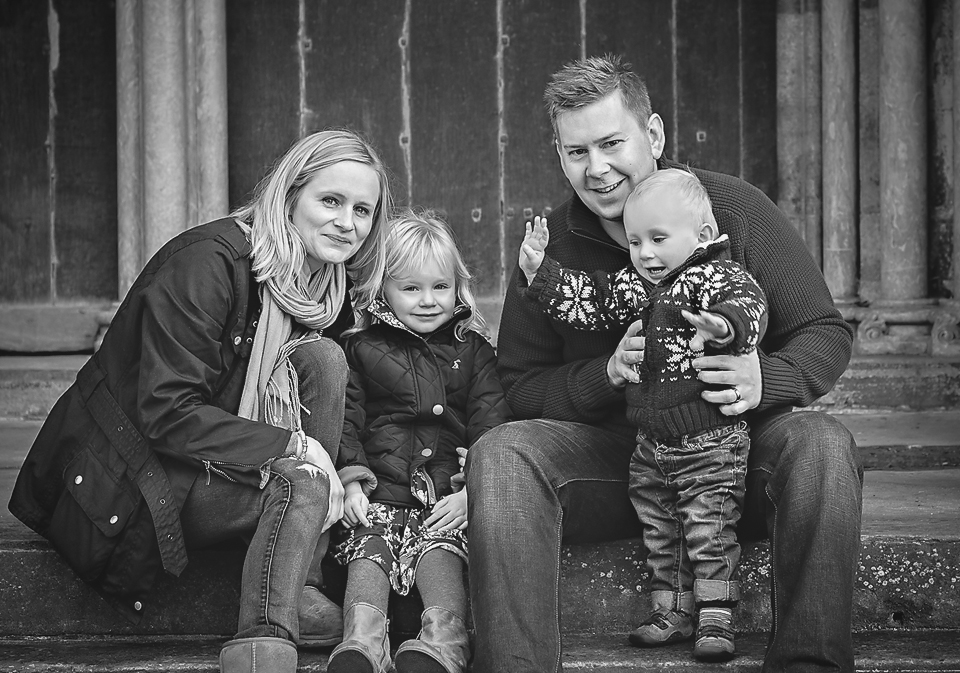 Family photograph of a Mum, Dad young daughter and baby son on the steps outside Salisbury Cathedral on a cold winters afternoon