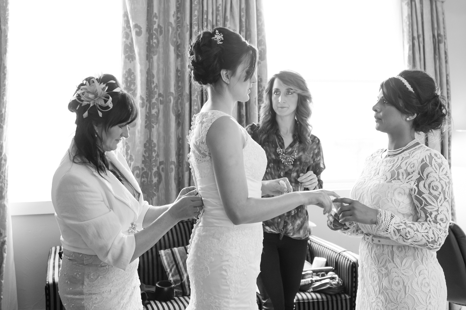 The bride is centre stage as her bridemaid, the hairdresser and her Mum encircle her and apply all the perfecting finishing touches to the bride's appearance