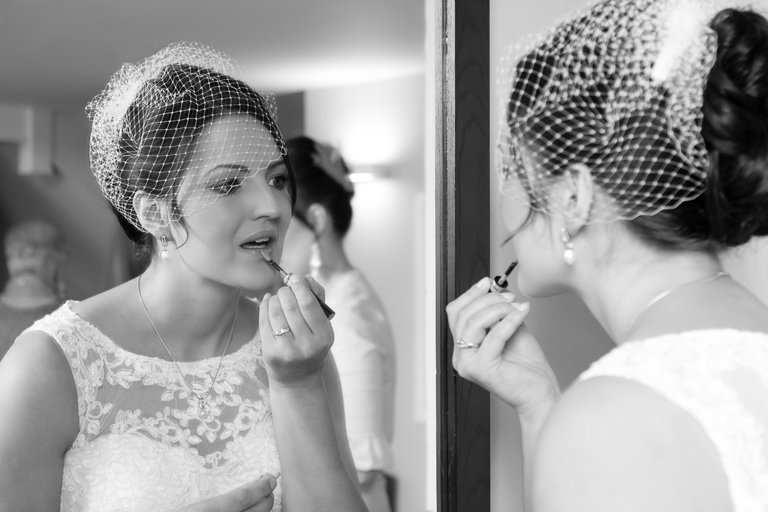 Classic wedding photograph of the bride applying lipstick in the mirror - you see the reflection of her face in the mirror and the side of her head in the foreground out of focus