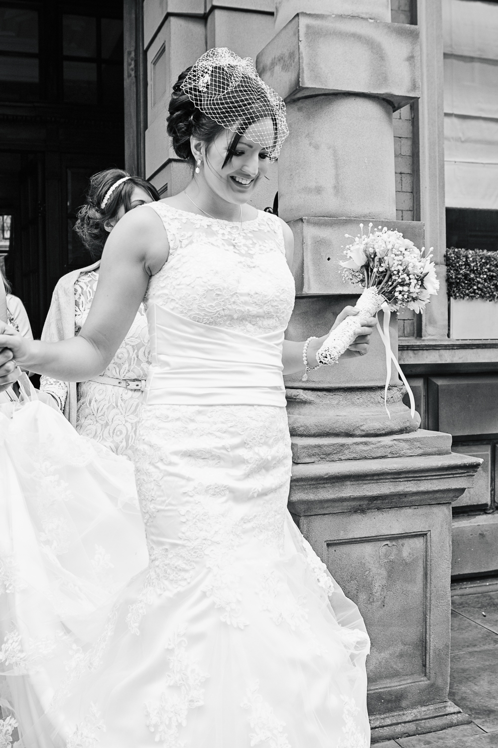 A black and white close up image of the bride leaving The Cathedral Quarter Hotel