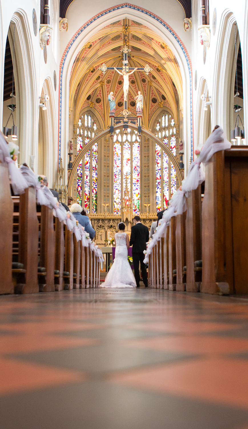 A portrait image of a bride and groom getting married in St Mary's Catholic Church in Derby