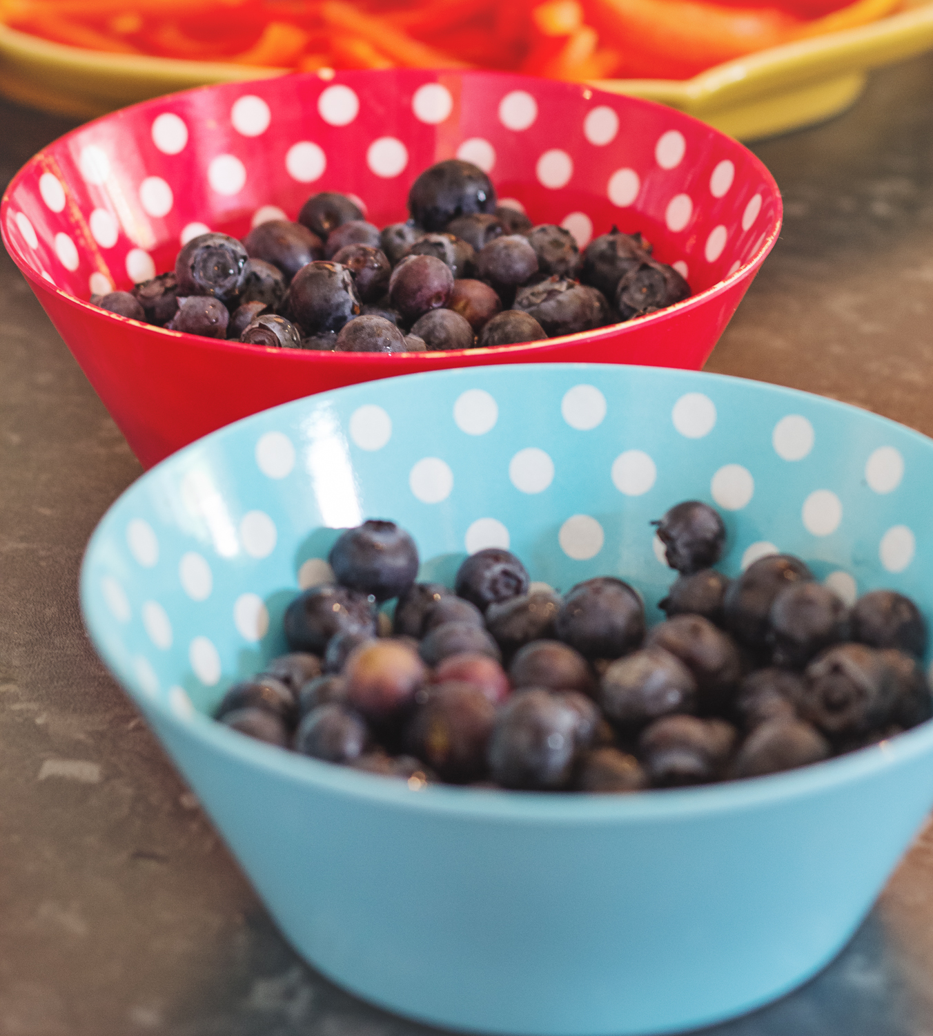 A close up photograph of healthy children's party food - blueberries in polka dot red and blue bowls