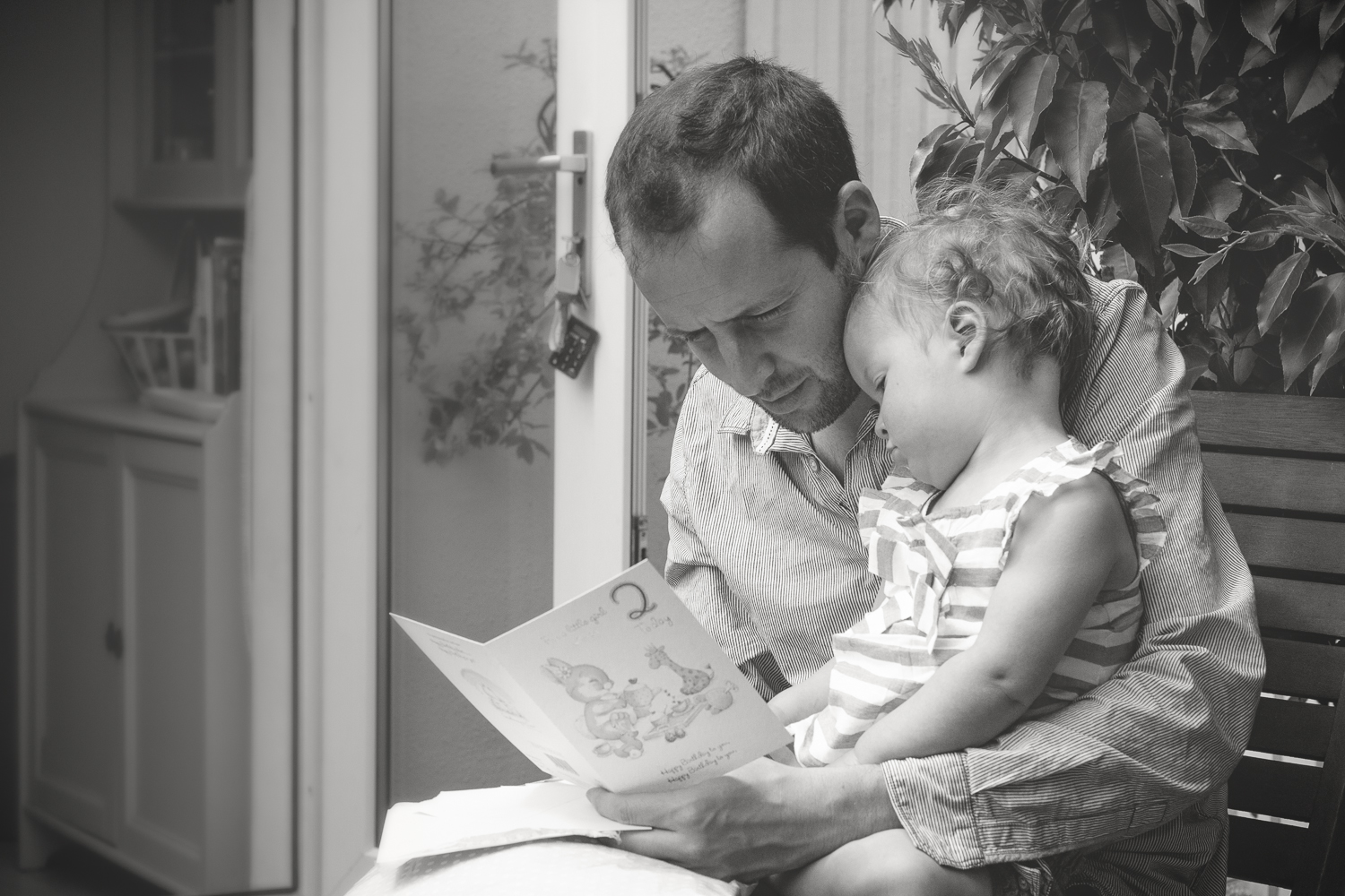 A dad reads a birthday card to his daughter on her second birthday in the garden