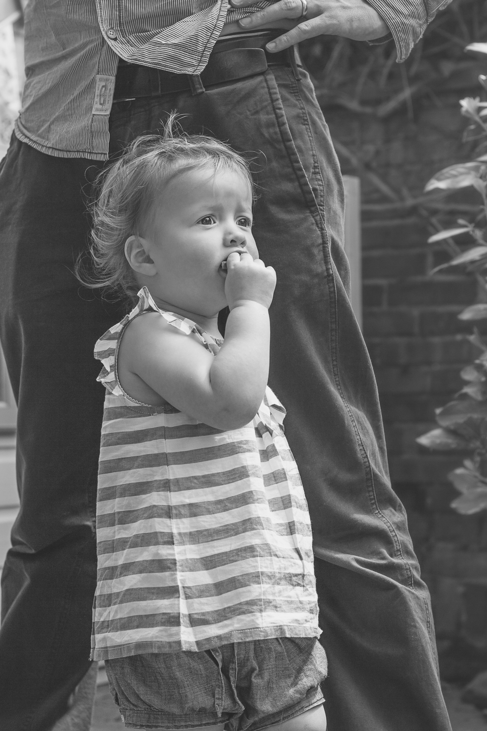 A little girl holds her hand to her mouth and hugs her dady's leg