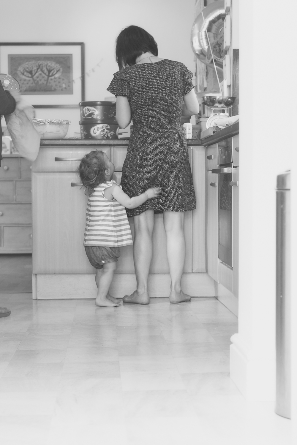 A little girl hugs her mummy's legs in the kitchen, as her mum prepares party food