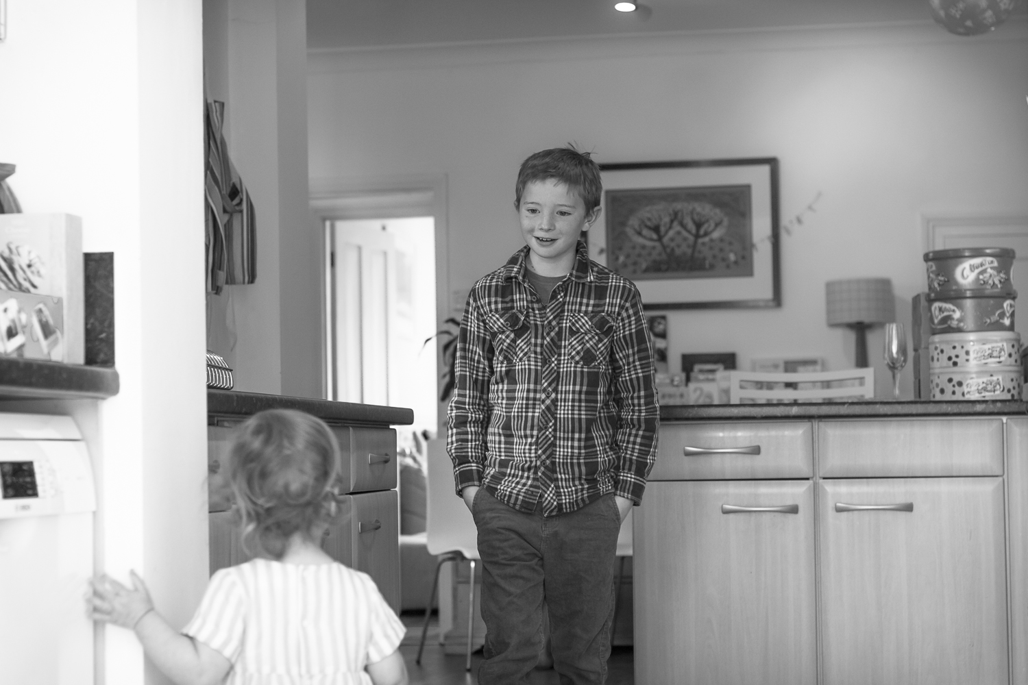 A two-year-olds 10-year-old uncle arrives at her party - they stand in the kitchen looking at eachother